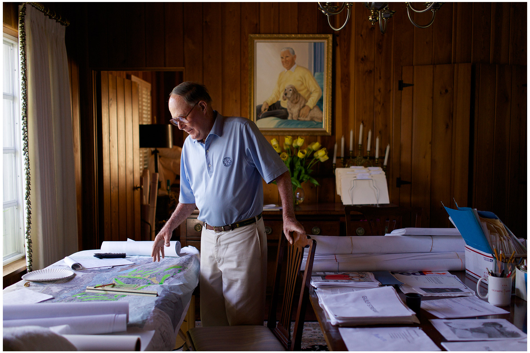 Pete Dye looking over a course layout in his dining room. Photographed for Golf World magazine.