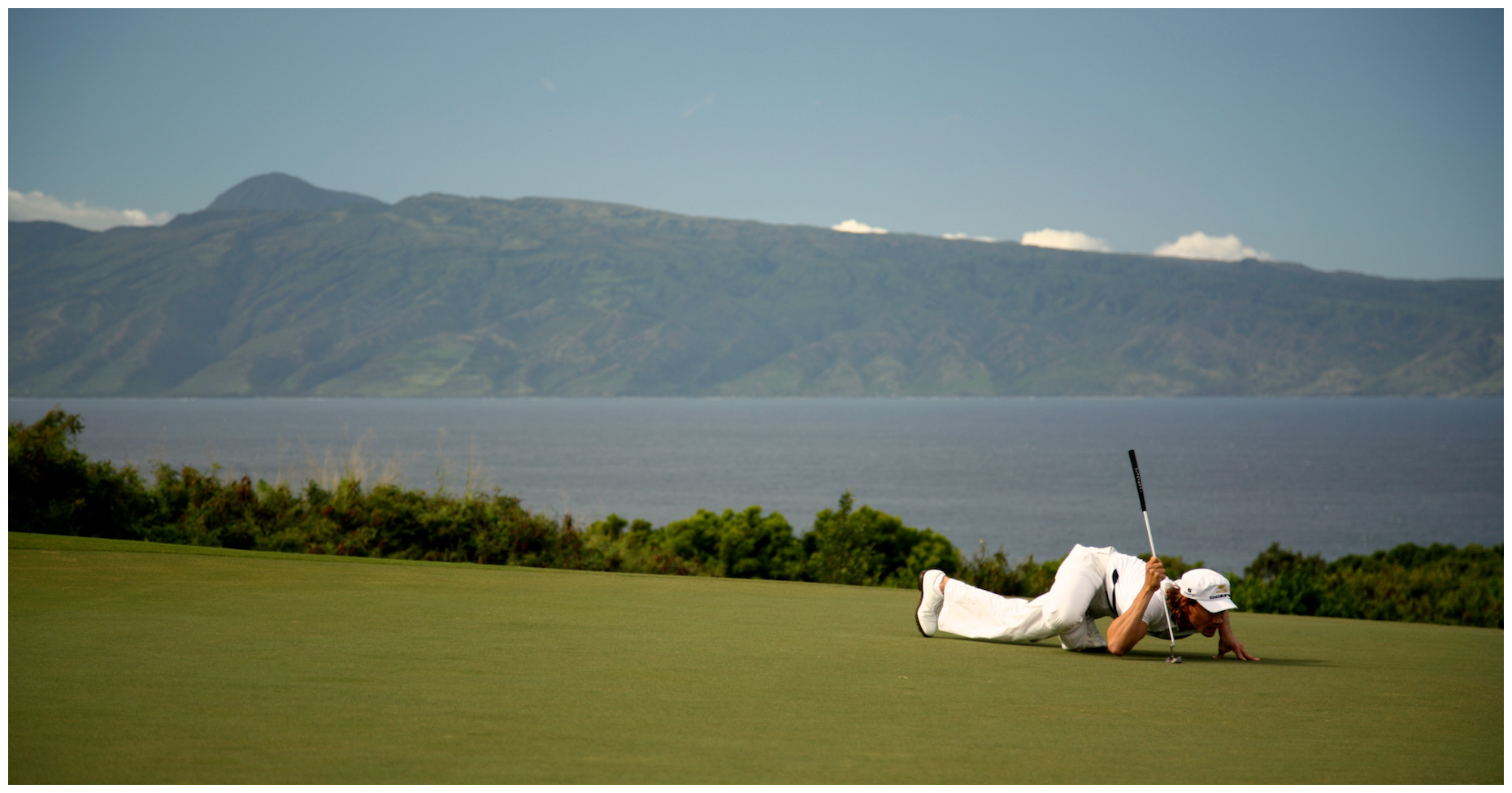 Camilo Villegas reads a putt in his signature style during a PGA tournament at the Plantation Course in Kapalua, Hawaii.